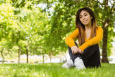 Woman sitting on grass at park — Stock Photo