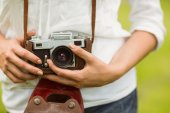 Mid section of woman holding vintage camera — Stock Photo