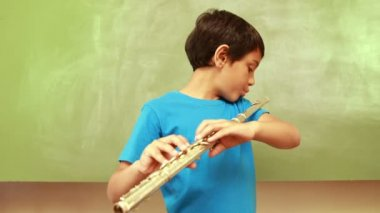 Pupil playing flute in classroom — Stock Video