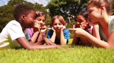 Pupils lying on the grass with hands together — Stock Video