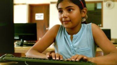 Cute little pupil looking at laptop in classroom — Stock Video