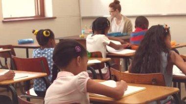 Élèves mignons écrit aux comptoirs dans la salle de classe — Vidéo