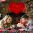 Couple with tea cups in front of lit fireplace — Stock Photo #64816707