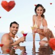 Cheerful couple having cocktails in the pool — Stock Photo #64818297