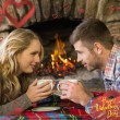 Couple with tea cups in front of lit fireplace — Stock Photo #64818501
