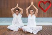 Attractive couple in white sitting in lotus pose — Stock Photo