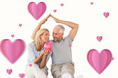 Happy couple sitting and sheltering piggy bank — Stock Photo