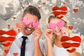 Couple holding pink hearts over eyes — Stock Photo