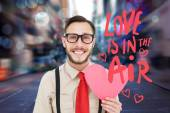 Composite image of geeky hipster smiling and holding heart card — Stock Photo