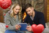 Couple using tablet pc in front of lit fireplace — Stock Photo