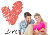 Atrakcyjna młoda para siedzi gospodarstwa serca — Zdjęcie stockowe