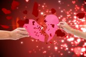 Composite image of hands holding two halves of broken heart — Stock Photo