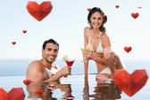 Cheerful couple having cocktails in the pool — Stock Photo