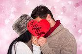 Ungt par kyssas bakom rött hjärta — Stockfoto