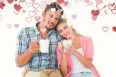 Attractive couple sitting holding mugs — Stock Photo
