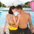 Couple sitting by swimming pool on a sunny day — Stock Photo #64820473