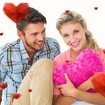 Couple sitting holding heart cushion — Stock Photo #64822413