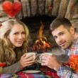 Couple with tea cups in front of lit fireplace — Stock Photo #64823707