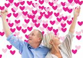 Happy mature couple with hands up — Stock Photo