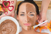 Peaceful brunette getting a mud facial applied — Stock Photo