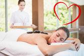 Beautiful woman receiving stone massage — Stock fotografie