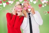 Silly couple holding hearts over their eyes — Stock Photo