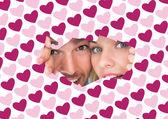 Young couple peeking through torn paper — Stock Photo