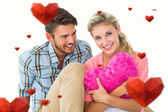Couple sitting holding heart cushion — Stock Photo