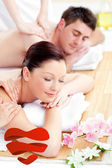 Composite image of young couple receiving a back massage — Stock Photo