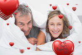 Happy middle aged couple under the duvet — Stock Photo
