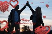 Silhouette couple holding up hands at dusk — Stock Photo