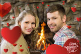 Smiling young couple in front of lit fireplac — Stock Photo