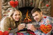 Couple with tea cups in front of lit fireplace — Stock Photo