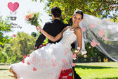 Newlywed couple sitting on scooter in park — Foto Stock