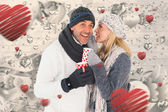 Happy couple in winter fashion holding mugs — Stock Photo