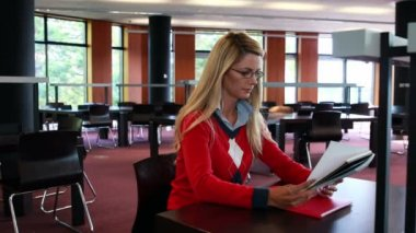 Student with reading glasses studying at library desk — Stock Video