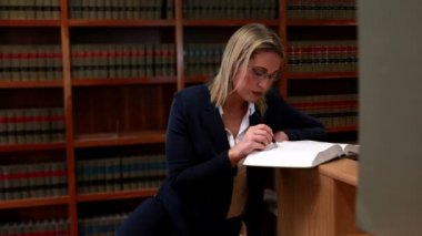 Librarian reading and noting in book — Stock Video