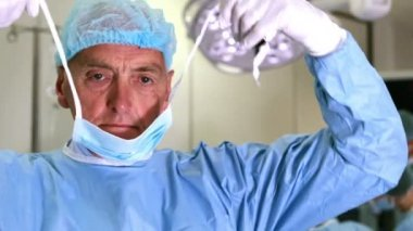 Medical professor in surgical gear putting on mask — Stock Video