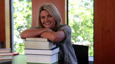Mature student leaning on pile of books — Stock Video
