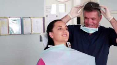 Smiling dentist examining a patient — Stok video