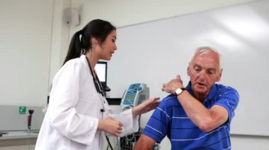 Doctor talking to patient with shoulder pain — Stock Video