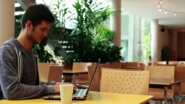 Smiling student sitting and using his laptop — Stock Video