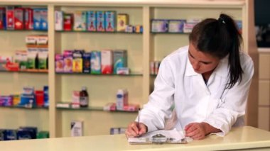 Junior pharmacist writing on clipboard — Stock Video