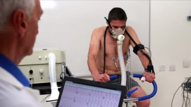 Man on exercise bike watched by doctor — Stock Video