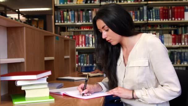 Estudiante morena sentada en el escritorio, escribiendo en el Bloc de notas — Vídeo de stock