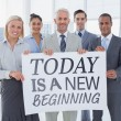 Composite image of business team holding large blank poster — Stock Photo #65235919