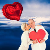 Older affectionate couple holding red heart — Stock Photo