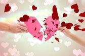 Hands holding two halves of broken heart — Stock Photo