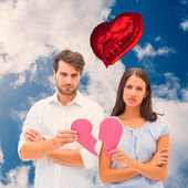 Upset couple holding two halves of broken heart — Stock Photo