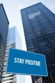 Stay positive against low angle view of skyscrapers — Stock Photo